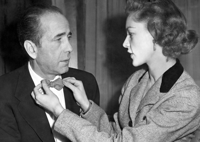 Actress Lauren Bacall, 27, adjust the bowtie of her husband Humphrey Bogart, 50, at a reception in Claridge's Hotel, London. Date: 16/04/1951