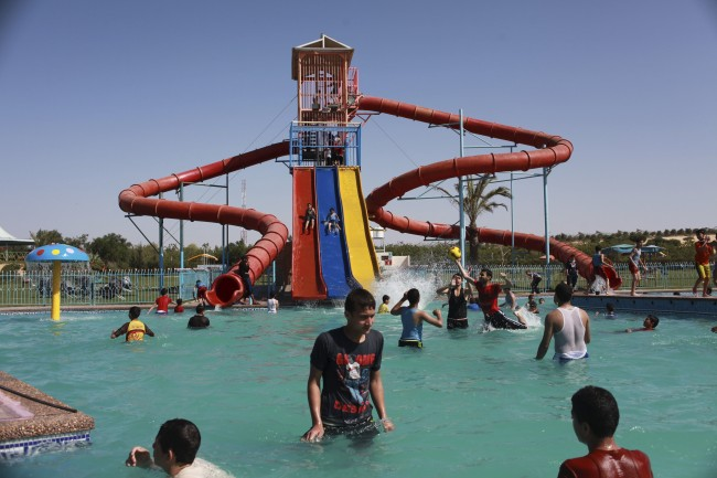 Palestinian boys play on a water slide as others have a sunbath at a swimming pool in Asdaa city, Khan Younis, southern Gaza Strip, Monday, April 28, 2014. (AP Photo/Adel Hana)