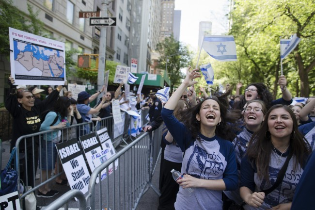 Marchers cheer as they pass along a barricade separating them from anti-Boycott, Divestment and Sanctions (BDS) movement protestors during the Celebrate Israel Parade, Sunday, June 1, 2014, in New York. Among the 35,000 marchers were New York Gov. Andrew Cuomo, New York City Mayor Bill de Blasio, Israeli diplomats and members of the Knesset, Israel's parliament. (AP Photo/John Minchillo)