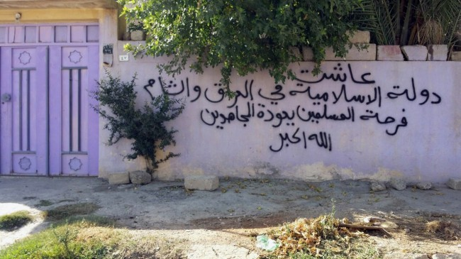 "This Saturday, July 19, 2014, photo, shows an empty house of a Christian family with Arabic writing that reads, ""Long live the Islamic State in Iraq and the Levant. Muslims are happy with the return of Mujahideen. God is Greater,"" in Mosul, 225 miles (360 kilometers) northwest of Baghdad, Iraq. Iraqi Prime Minister Nouri al-Maliki on Sunday condemned the Islamic State extremist group's actions targeting Christians in territory it controls, saying they reveal the threat the jihadists pose to the minority community's ""centuries-old heritage."" (AP Photo)"