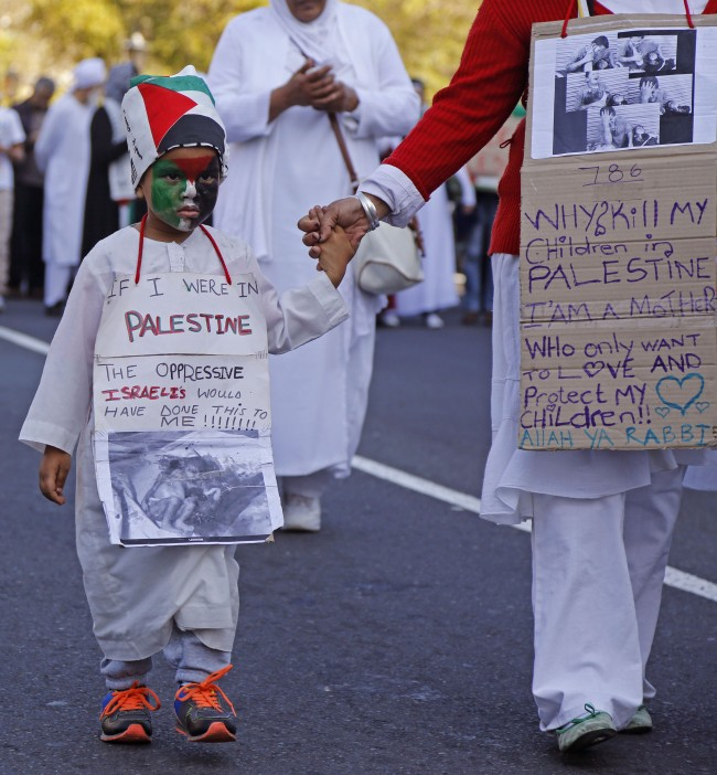 A child walks with his mother, as they forms part of the Palestinian supporters taking part in a rally against the Israeli occupation of the Palestinian territories in Cape Town, South Africa, Saturday, Aug. 9, 2014. Thousands of anti-Israel protestors took to the streets marching on the South African parliament building to protest against Israeli occupation and strikes on Gaza, in recent time. (AP Photo/Schalk van Zuydam)