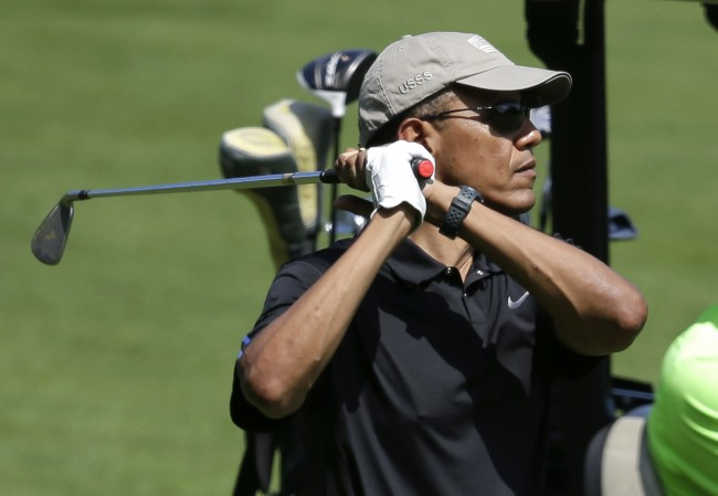 President Barack Obama follows through on a swing while golfing at Farm Neck Golf Club, in Oak Bluffs, Mass., on the island of Martha's Vineyard, Sunday, Aug. 10, 2014. President Obama fled Washington for his familiar spot on Martha's Vineyard for a two-week summer vacation. (AP Photo/Steven Senne)