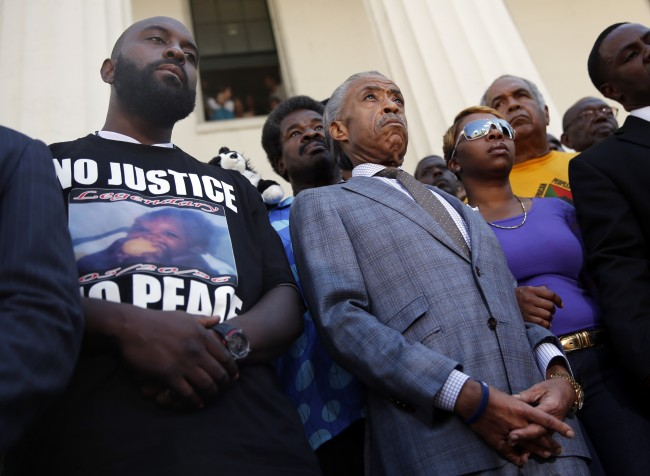 Civil rights leader Rev. Al Sharpton, center, stands with the parents of Michael Brown, Lesley McSpadden, right, and Michael Brown Sr., left, during a news conference outside the Old Courthouse Tuesday, Aug. 12, 2014, in St. Louis.
