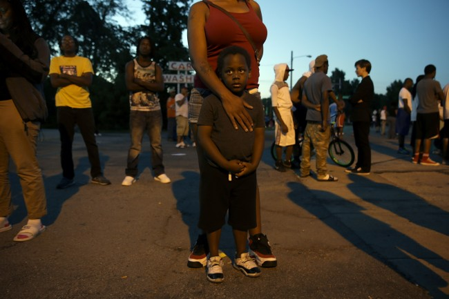 Jeremiah Parker, 4, stands in front of his mother, Shatara Parker, as they attend a protest Wednesday, Aug. 13, 2014, in Ferguson, Mo