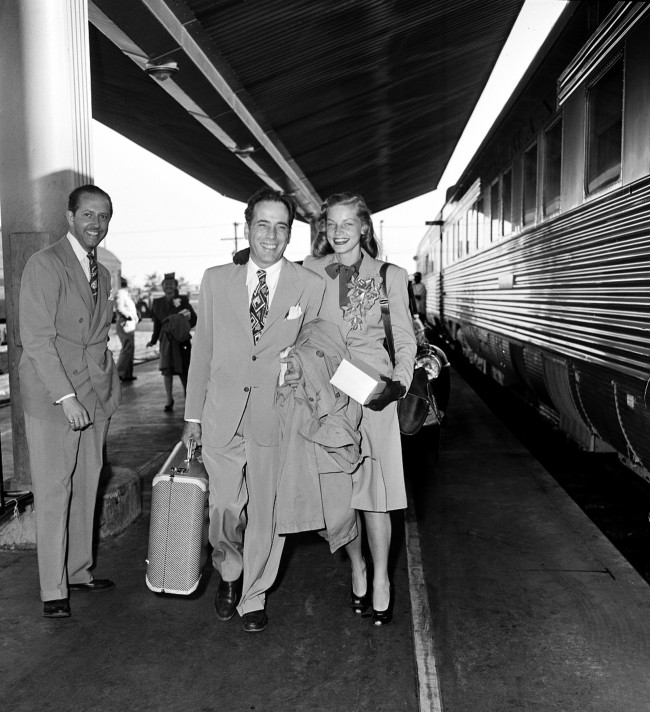 Actor Humphrey Bogart and actress Lauren Bacall are shown at a train station before they board the Santa Fe in Los Angeles, Ca., on May 18, 1945. The couple will travel to Mansfield, Ohio, where they will get married at a friend's farm.