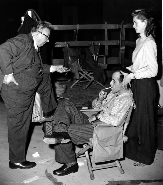 "Actor Humphrey Bogart, lighting cigarette, actress Lauren Bacall, massaging her husband's head, and cameraman Karl Freund relax on the set of ""Key Largo"" in Hollywood, Ca., on Jan. 19, 1948. (AP Photo)"