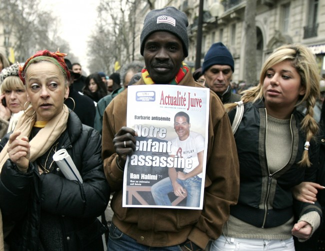 "Demonstrators take part in a march in Paris, the French capital, Sunday, Feb. 26, 2006 to show opposition to racism and anti-Semitism after the brutal killing of Ilan Halimi, a Parisian Jew, seen in the placard. The sign says in French says ""Our child murdered"". (AP Photo/Francois Mori)"