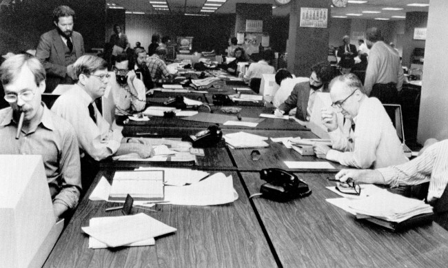 "The newsroom at the New York Times is seen as editorial staffers work feverishly to prepare a Monday edition, in this Nov. 5, 1978 file photo. A reader-submitted question related to how newsrooms are alerted to breaking news stories is being answered as part of an Associated Press Q&A column called ""Ask AP."" (AP Photo/Ron Frehm, File)"