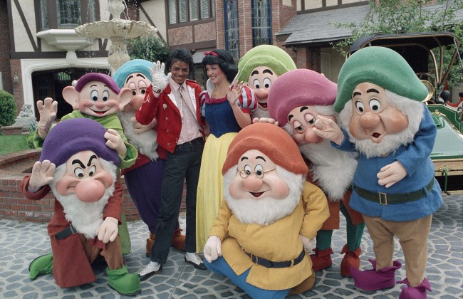 Superstar Michael Jackson is surrounded by fantasy as he stands with Snow White and Dopey, of the Seven Dwarfs fame on Friday, April 27, 1984 in Jackson's Encino, California home. The Disney characters presented Jackson with a one-of-a-kind display featuring the characters in a scene representative of the 1937 classic film. (AP Photo/Wally Fong)