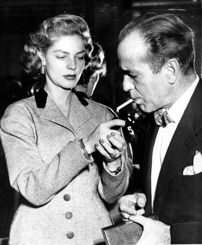 Actress Lauren Bacall lights a cigarette for her husband, actor Humphrey Bogart, at a press reception at London's Claridges Hotel, England, on April 16, 1951. (AP Photo)