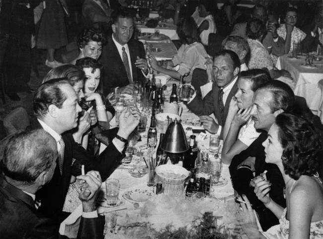 Some members of the Holmby Hills Rat Pack, a group of exceedingly well heeled Bohemians that include screen stars and millionaires from Hollywood's super-ritzy Holmby Hill section, are seen sitting at a table having cocktails at the Copa Room in Hollywood, Oct. 15, 1956.. Shown left to right are Humphrey Bogart; producer Sid Luft; Lauren Bacall; Judy Garland; Ellie Graham; agent Jack Entratter; restaurateur Mike Romanoff (partly hidden); Frank Sinatra; Mrs. Romanoff; actor David Niven; and Mrs. Niven. (AP Photo)