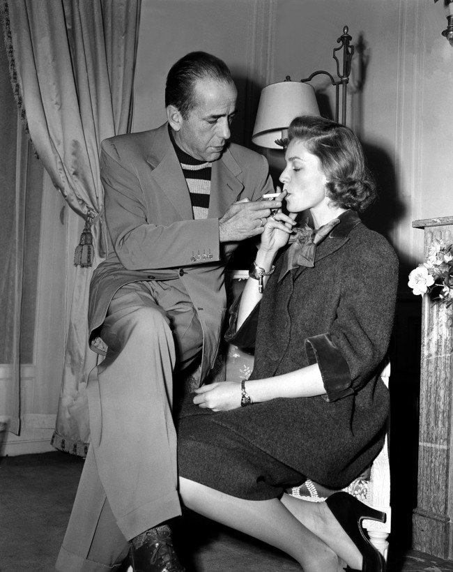 Actor Humphrey Bogart lights a cigarette for his wife, actress Lauren Bacall, in their room at the Ritz Hotel in Paris, France, during their vacation on March 26, 1951.
