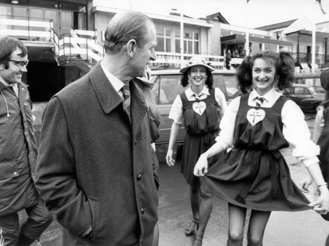 "The Duke of Edinburgh, Chancellor of Cambridge University, visiting the Cambridge crew for the Boat Race. He is surrounded by a group of St Trinians 'schoolgirls', who were there to publicise their new film ""Wildcats of St Trinians"". Date: 28/03/1980"
