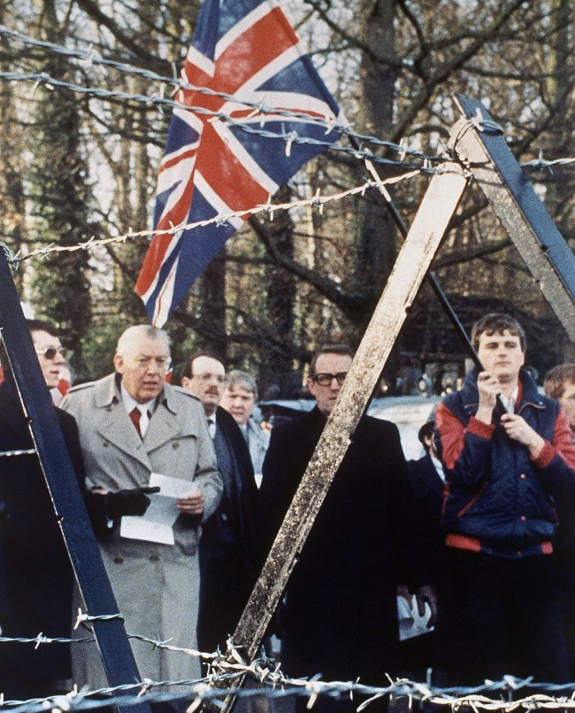 Northern Ireland Loyalist leaders including the Reverand Ian Paisley, in (light coat); Harold McCusker (dark coat); and Peter Robinson, (dark spectacles) approach a barbed wire barricade surrounding Stormont Castle, near Belfast, Northern Ireland in December 1985. They were protesting against a meeting at the castle between British and Irish government ministers, implementing the newly-signed Anglo-Irish Accord which for the first time gives the Dublin government a consultative role in the running of Northern Ireland's affairs. (AP Photo/Peter Kemp)