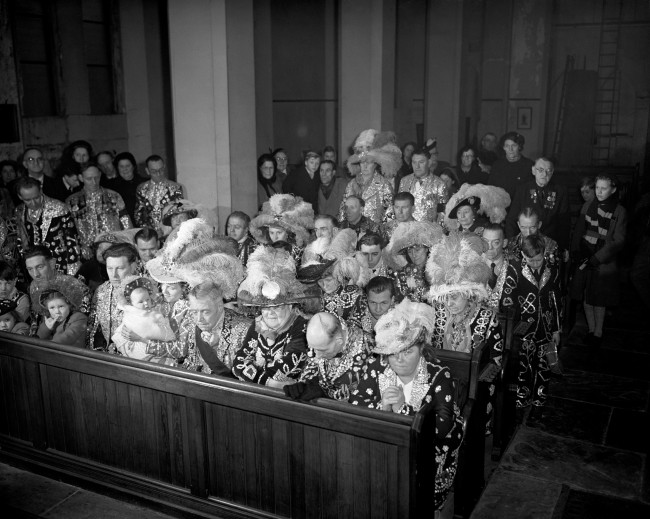 London's costermongers and their families - the famed Pearly kings and queens - in their costumes, pray for the late King George VI, at a special memorial service in St. Mary Magdalene Church, Southwark, London.   Date: 17/02/1952