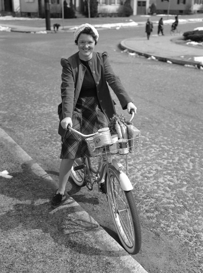 The market-going housewife on a bicycle is helping Uncle Sam's wartime economy in Melrose, Mass., on March 20, 1942. Mrs. Roland Zabel, wife of a lighting engineer, was one of the first in the town to start the women riding to the grocery store for the day''s supplies. She is shown on her bike with the day's provisions packed in the basket. She is not only saving automobile tires and gasoline, but she is also saving on paper bags. (AP Photo/George H. Hill)