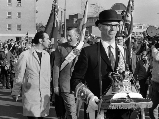Protestant leader Reverend Ian Paisley, behind crown bearer, leads the Protestant Easter March through Armagh, Northern Ireland, while British troops stand guard on Easter Saturday, April 10, 1971. (AP Photo/Dennis Lee Royle