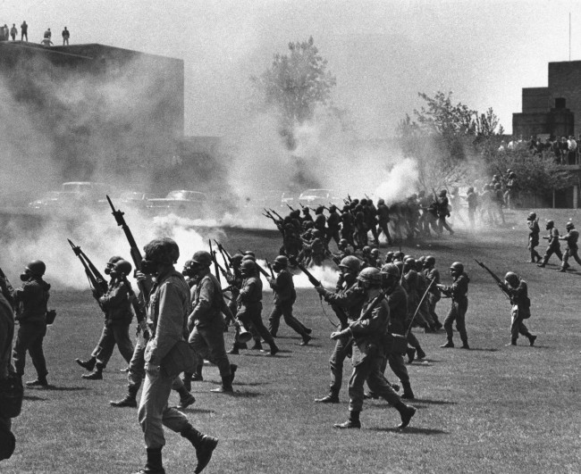In a May 4, 1970 file photo, a group of youths cluster around a wounded person as Ohio National Guardsmen, wearing gas masks, hold their weapons in the background, on Kent State University campus in Kent, Ohio.