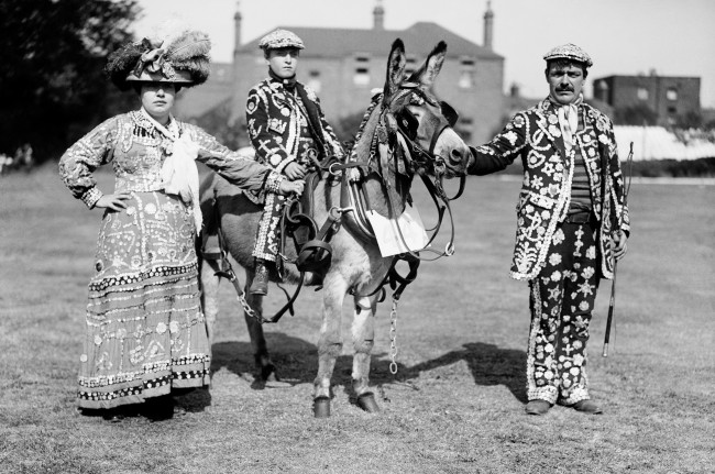 'Costers' in Pearlies - a family party at Peckham Derby show. 'Costers', or 'Costermongers' are street sellers of fruit and vegetables. Those elders respected by the Costermongering families are elevated to the position of Pearly Kings and Queens and their non-public role is to keep the peace between the   Date: 01/06/1911
