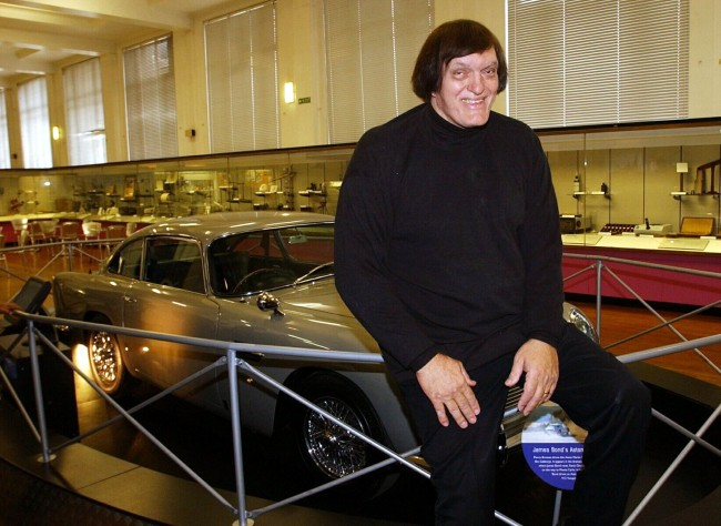 Richard Kiel, who played 'Jaws' in James Bond movies, poses with an Aston Martin from 1995 movie, Golden Eye, at the Science Museum, London. The exhibition is a retrospective of Bond memorabilia, coinciding with the launch of the new movie.  Ref #: PA.1653449  Date: 20/11/2002
