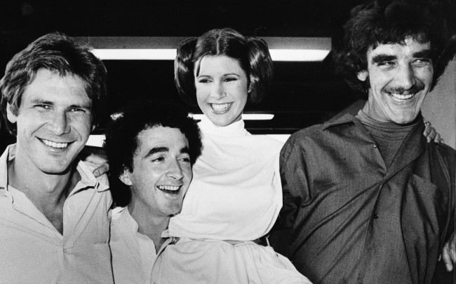 "In this Oct. 5, 1978 file photo, actors featured in the ""Star Wars"" movie, from left, Harrison Ford who played Han Solo, Anthony Daniels who played the robot C3P0, Carrie Fisher who played the princess, and Peter Mayhew who played the Wookie, Chewbacca, are shown during a break from the filming of a television special presentation in Los Angeles."