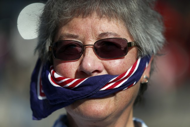 A free speech campaigner uses a British flag as a gag during a protest opposite the Houses of Parliament in central London, Tuesday, Oct. 8, 2013.