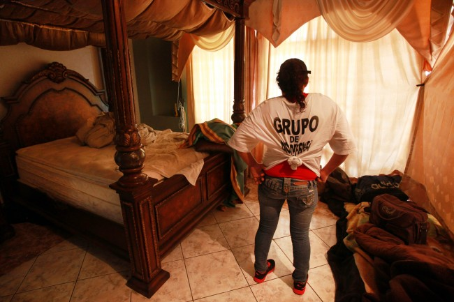 "A woman belonging to the Self-Defense Council of Michoacan, (CAM) inspects a bedroom in the abandoned home of an alleged member of the Templar Knights drug cartel in Paracuaro, Mexico, Friday Jan. 17, 2014. According to the vigilante group, the owner of the home was nicknamed ""El Botas"" or ""the Boots"". Vigilantes in Michoacan state insist they won't lay down their guns until top leaders of a powerful drug cartel are arrested, defying government orders as federal forces try to regain control in a lawless region. (AP Photo/Felix Marquez) Date: 17/01/2014"