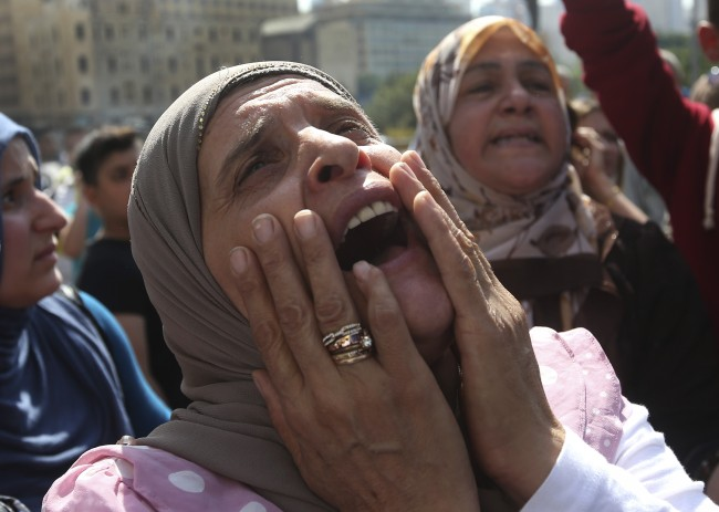 The mother of a missing Lebanese soldier who was kidnapped by Islamic State militants, shouts slogans against the Lebanese cabinet during a demonstration to demand action to secure the captives' release, in front the Lebanese government building, in downtown Beirut, Lebanon, on Thursday, Sept. 4, 2014. Lebanon's government is forming a crisis committee to handle the case of some two dozen members of the security forces held captive by Syrian militants amid escalating criticism over its response to the hostage affair. Militants, including from the Islamic State extremist group, seized around 30 soldiers and policemen after overrunning a Lebanese border town in early August. (AP Photo/Hussein Malla)