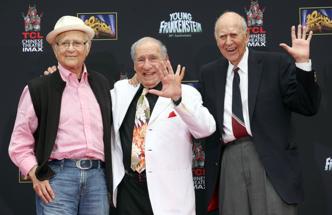 "Filmakers Norman Lear, left, Mel Brooks sporting a prosthetic finger, and Carl Reiner, right, pose for a photo during a Hand and Footprint ceremony for Brooks on the 40th anniversary of the movie ""Young Frankenstein,"" in front of the TCL Chinese Theatre in Hollywood section of Los Angeles, Monday, Sept. 8, 2014. (AP Photo/Nick Ut)"