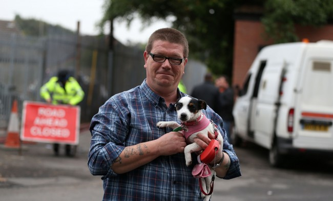Michael Parker, a local resident who in the past has homed dogs from the centre, holds Misty the Jack Russell outside Manchester Dogs' Home, Manchester, after a blaze killed more than 50 dogs.