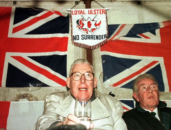 "In this Friday April 4, 1997 file photo Northern Ireland's Democratic Unionist Party leader Ian Paisley prepares to address a crowd of around 1000 loyalist supporters, as they gathered for a ""right-to-march"" rally in Portadown, Northern Ireland. Paisley the fiery Protestant leader has died in Northern Ireland aged 88 his wife Eileen said Friday Sept. 12, 2014. Much like the Ulster weather, Ian Paisley could offer beaming sunshine one minute, stinging hailstones the next. The international image of Paisley _ that of Northern Ireland's most dangerous demagogue, a belligerent bigot committed to keeping Irish Catholics at bay and out of power _ was well-documented in its own right. But understanding the worst of the public Paisley wouldn't prepare you for meeting him in the flesh. (AP Photo/File) Ref #: PA.20895751  Date: 22/03/2007"