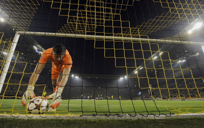 Arsenal's goalkeeper Wojciech Szczesny lifts the ball after Dortmund's Ciro Immobile, scored his side's opening goal during the Champions League group D soccer match between Borussia Dortmund and Arsenal in Dortmund, Germany, Tuesday, Sept.16, 2014. (AP Photo/Martin Meissner)