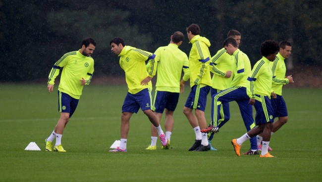 Chelsea's Cesc Fabregas (left) and Diego Costa (second left) warm up with their team mates during a training session at Cobham Training Ground, Surrey. Picture date: Monday September 29, 2014,