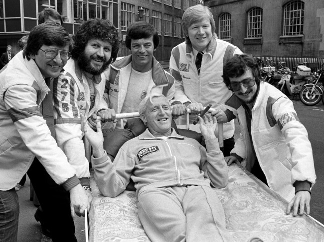 Radio One Disc Jockeys take time off to push Jimmy Savile from Broadcasting House to Park Lane by bed, in aid of the Variety Club of Great Britain and the Outward Bound Trust. (L-R) Simon Bates, Dave Lee Travis, Tony Blackburn, Kid Jensen and Steve Wright. Ref #: PA.2142892  Date: 16/04/1980