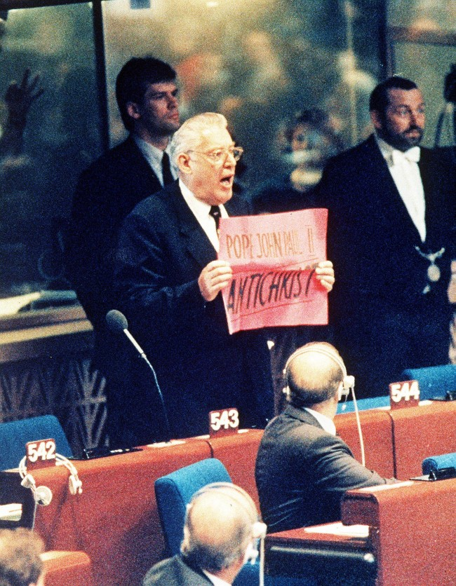"Northern Ireland's DUP leader and Moderator of the Free Presbyterian Church Rev. Ian Paisley interupts Pope John Paul II at the start of his allocution at the European Parliament in Stasbourg, France, Oct. 11, 1988. Paisley holds a banner reading ""John Paul II Anti-Christ"". (AP Photo)"