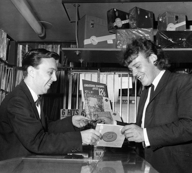 Blues and Northern Soul singer Joe Cocker (r) buys a copy of his own record from a London record shop Date: 01/09/1964