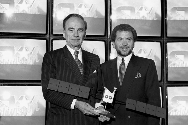 Newspaper tycoon Rupert Murdoch (left) and millionaire businessman Alan Sugar hold a model of the Astra Satellite at a London press conference, where Mr Murdoch announced he had signed a 10-year lease for three new satellite channels. Mr Sugar's Amstrad company is to manufacture a satellite dish and receiver aimed at the mass market. Ref #: PA.6164629  Date: 08/06/1988