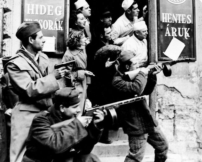 Patrons and clerks at a local store get a grandstand view of the action as men of the Hungarian revolutionary forces take aim at members of the Communist secret police, on November 2, 1956, during an anti-Communist uprising in Budapest, Hungary. The mass revolt was later crushed as Soviet troops and tanks encircled and captured the Hungarian capital and several other cities. (AP Photo)