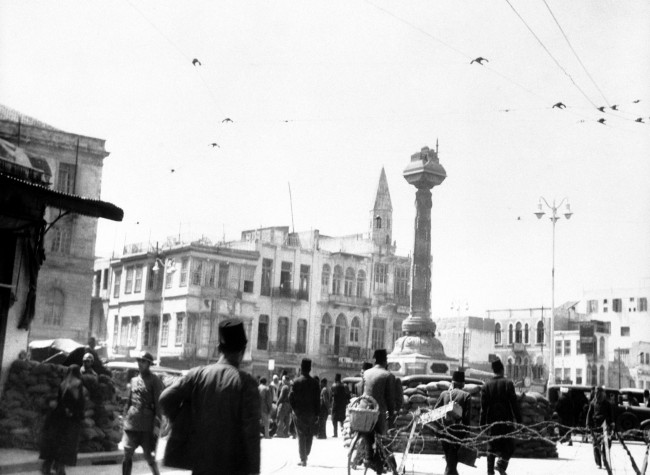 The French military authorities have taken over control of the city of Damascus, the capital of French Syria, following the disorders resulting from the General strike and the resignation of the government. Barbed wire barricades and military guards in the Place Des Martyrs, the principal square of Damascus on March 29, 1939, after the city had been placed under military control. (AP Photo)