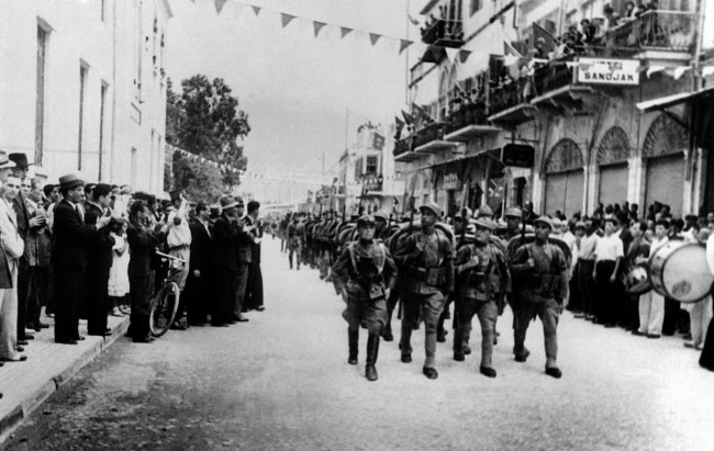 France and Turkey concluded a military agreement over the Sanjak of Alexandretta, territory between Asiatic Turkey and Syria, to ensure internal security. Agreement was on parity basis and 2,500 French, non-Syrian troops, and 2,500 Turkish troops are being kept available now. Happy Turkish crowds applauding the march past of the Turkish troops as they entered the Sanjak of Alexandretta, Turkey on July 1, 1938. Streets and balconies are be flagged with the Turkish red flag with white crescent which they had not seen in the territory for nearly 20 years. (AP Photo) Ref #: PA.11614969  Date: 01/07/1938