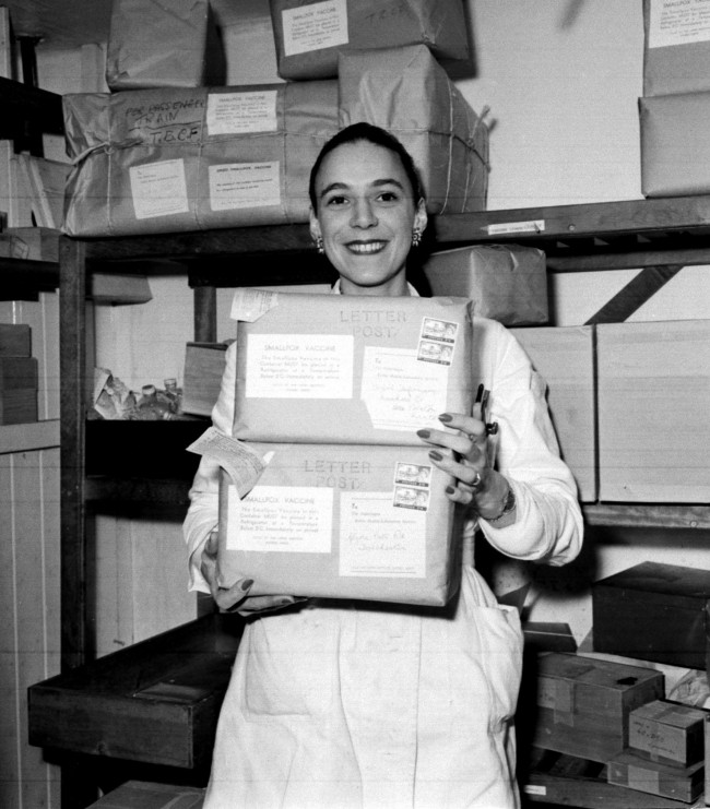 Sally Hankey, a junior technician at the Lister Institute of Preventive Medicine, Elstree, Herts, carrying cases of smallpox vaccine before their despatch to all parts of the country. Date: 16/01/1962