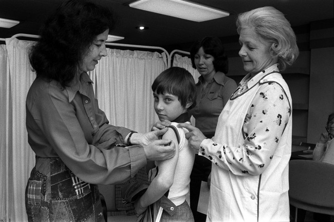 Philip Stubbs, 10, from Stoke on Trent gets a smallpox jab at the special unit set up at Birmingham Airport before a trip to Malta with his Mother, after 8 more countries demanded smallpox certificates after a female laboratory worker was found with the disease. Date: 31/08/1978