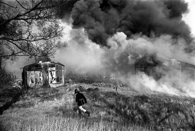 A fireman runs through the smoke as the disused Witton Isolation Hospital at Birmingham blazes after a fire had been set to rid the city of a smallpox threat. Date: 03/05/1967