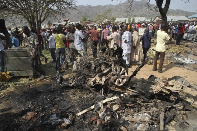 In a Sunday, Dec. 25, 2011 file photo, onlookers gather around a car destroyed in a blast next to St. Theresa Catholic Church in Madalla, Nigeria after an explosion ripped through a Catholic church during Christmas Mass near Nigeria's capital Sunday, killing scores of people, officials said. A radical Muslim sect, Boko Haram, claimed the attack and another bombing near a church in the restive city of Jos, as explosions also struck the nation's northeast. Boko Haram's insurgency started with robed men on motorcycles killing their enemies one at a time across Nigeria's remote and dusty northeast. Now the radical Muslim sect's attacks have morphed into a nationwide sectarian fight. (AP Photo/Sunday Aghaeze, File)