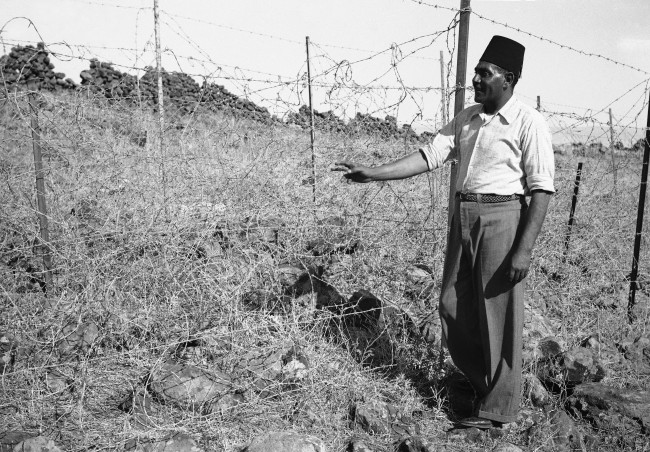 An Arab stands beside a section of ìTegartís Iron wallî in Israel in 1938, erected by Sir Charles Tegart to keep marauding Arabs out of Palestine. The fence, three strains of barbed wire on angular iron supports. Stretches for 60 miles on the Syria-Lebanon borders and cost $ 500,000. (AP Photo/James Mills )