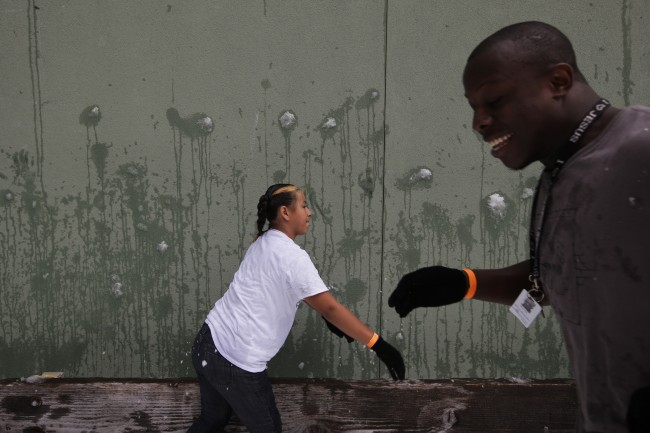 Passion Guzman, 11, center, throws a snow ball during the annual Christmas in July event at the Union Rescue Mission in the Skid Row area of Los Angeles, Wednesday, July 10, 2013. (AP Photo/Jae C. Hong)