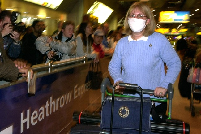 Sandra Perry from Sutton, Surrey, wears a face mask as she arrives back at Heathrow Airport, on a flight from Beijing, China. *..The Government has been urged to classify Sars alongside cholera and smallpox so that people arriving in the UK with symptoms could be detained for treatment as the Shadow health secretary Dr Liam Fox said Britain s response so far to the outbreak had been 'feeble, complacent and irresponsible'. But the Chief Medical Officer Sir Liam Donaldson said all six cases in Britain so far had been detected quickly and brought under control.   Date: 24/04/2003