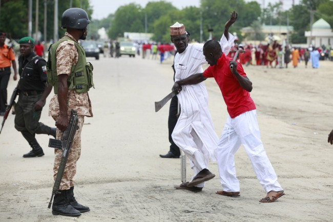 "In this photo taken Thursday, Aug. 8, 2013, Nigeria security forces, left, watch as a member of the ""Civilian JTF"" right, pushes a man during an event, in Maiduguri, Nigeria. The battered old car, cutlasses and nail-studded clubs poking out of its windows, careens down the road and squeals to a stop. Its young occupants pile out, shouting with glee, and set up a roadblock. They are part of a vigilante force that has arisen here as a backlash against Boko Haram, the Islamic extremist network responsible for 1,700 deaths in Nigeria since 2010, according to a count by The Associated Press. (AP Photo/Sunday Alamba)"