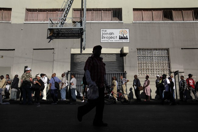 People form a line to get a free hotdog from a charity organization in the Skid Row area of Los Angeles on Tuesday, July 23, 2013. (AP Photo/Jae C. Hong)