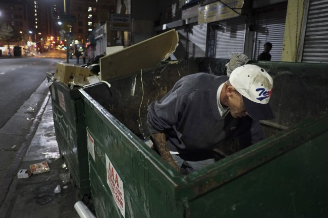 Shawn McGray, a 34-year-old homeless man, looks through a dumpster for anything useful in the Skid Row area of Los Angeles, Thursday, March 21, 2013. McGray said his goal is to save enough money to move into a small apartment with his girlfriend. (AP Photo/Jae C. Hong)